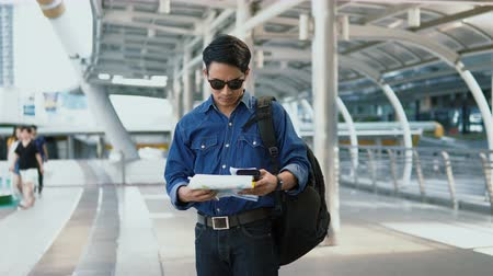 Dolly and close up Asian handsome young man wearing a shirt jeans and sunglasses is checking point on paper map and smartphone before walking away