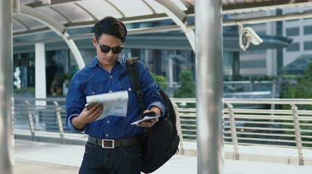 Locked shot and close up Asian young man wearing a shirt jeans and sunglasses is walking in frame and checking point on paper map before walking away