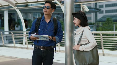 Dolly shot and close up Asian young man and pretty woman looking for a destination to go against the paper map in hand before hand in hand and walked out