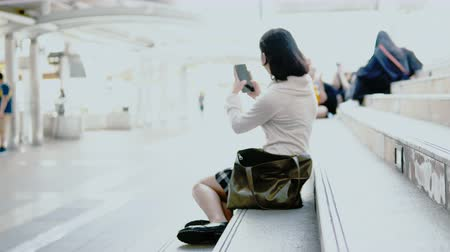 Long shot with scene Asian young pretty girl sitting on the steps of the public place, she use Handheld shooting herself. Careless and unguarded bag, and a stolen wallet to elicit Vídeos