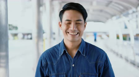 Locked shot with portrait Asian handsome man looking at camera and used hand adjust collar shirt and smiled happily, blurry background