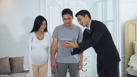 The spouse walking into the showroom, salesman is using the tablet to the client product information to customer, And recommended customers to test the comfortable by sit down on the beautiful couch Stok Video