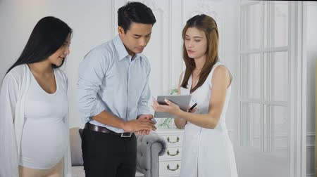 The young man holding a pregnant wife to see the furniture in the showroom. Young sales employee make the catalogue with the tablet and recommended customers sit down on the beautiful couch Stok Video
