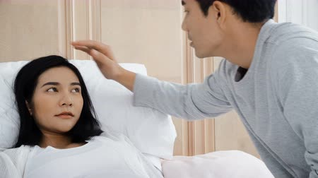 Medium shot of Young man use thermometer to his wife pregnant lying on bed with care Stok Video