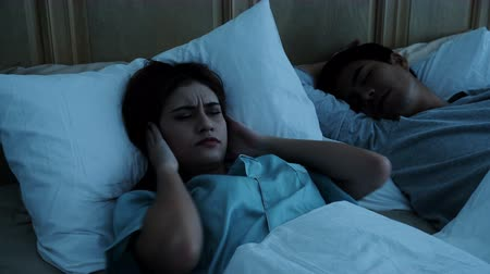 Medium shot the young woman is disturbed sleep from snoring husband sleeping nearby on bed in night time, then she used a pillow off the ears with a nuisance