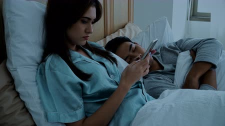 Medium shot the young woman used smartphone on the bed and her husband sleeping nearby in bed room at night time, social addict concept Stok Video