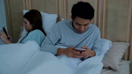Asian young married couple laying in bed chatting on social media addicted to smartphones ignoring each other in bedroom at night, social addict concept Stok Video