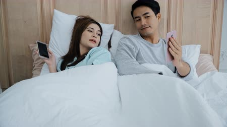 ignoring : Asian young married couple laying in bed and used application chatting on social media by smartphones and talking together in bedroom, social addict concept Stock Footage