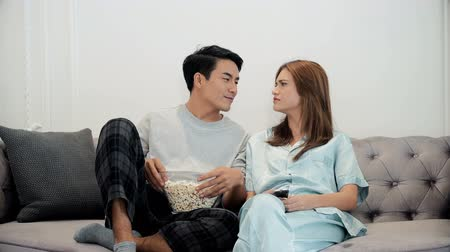 Young man and pretty woman sitting on the couch in the living room, they are enjoy to watch television. wife use remote control to change the channel and husband eating popcorn