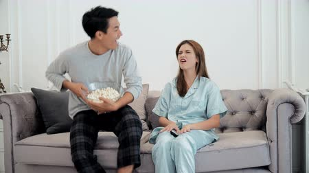 frustrate : The young couple excited to cheer for sports television program husband cheerful when the cheer team won, and frustrated wife, they are watch television and eating popcorn