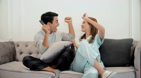 family watching tv : The young couple excited to cheer for sports television program and cheerful when the cheer team won, they are watching television and eating popcorn together