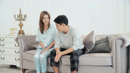 The beautiful wife came up to husband who was watching television on the couch. husband felt disappointed when his wife is not pregnant Stok Video
