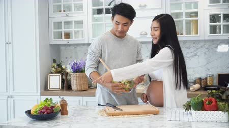 Locked the young husband happy to cooking salad for his pregnant wife in the kitchen, family concept Stok Video