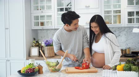 Young pregnant use knife to slicing red sweet pepper,  husband help her slice and put into glass of vegetables salad