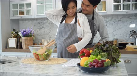 The young husband is putting an apron on his pregnant wife before cooking in kitchen
