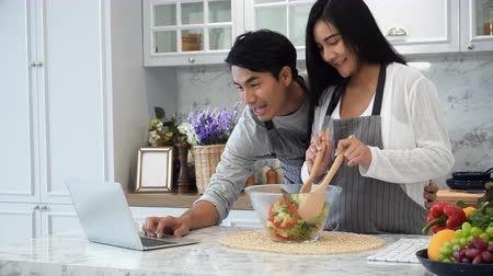 The young husband with his pregnant wife are wearing an apron and use laptop computer while cooking in kitchen