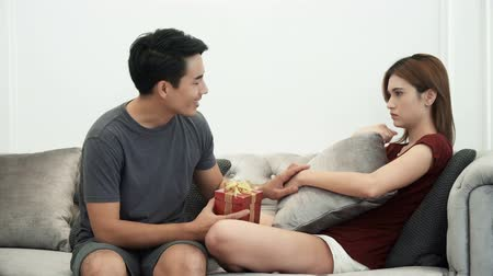 apologize : The young man hiding gift box behind to apologize his wife.  Beautiful wife sitting and sad on the sofa, They are talk to reconcile, and happy together