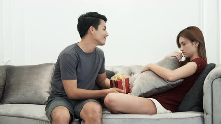 apologize : The young man hiding gift box behind to apologize his wife.  Beautiful wife sitting and Sad on the sofa, They are talk to reconcile, and happy end together Stock Footage