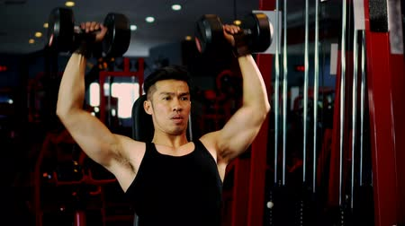 Locked shot handsome muscular man doing exercise with weight 40 lbs. of dumbbells, He sit and lifts up heavy weights over head on fitness training  at gym, healthy fitness concept