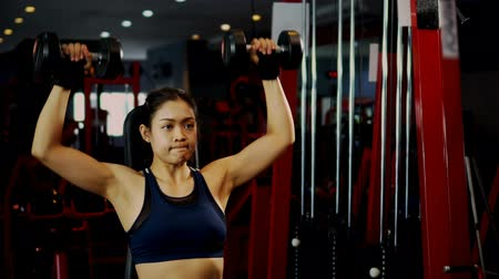 Locked shot the strong muscular female doing exercise with weight of dumbbells, she sit and lifts up heavy weights over head on fitness training at gym, healthy fitness concept Vídeos