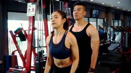 Hand held and close up pretty fitness woman and young trainer man are exercising building muscles with lifting two arm with heavy dumbbells  in sport gym, fitness and healthy concept
