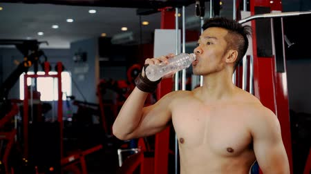 Locked shot with shirtless young muscular man drinking water from bottle at gym equipment in fitness club, fitness and healthy concept Stockvideo