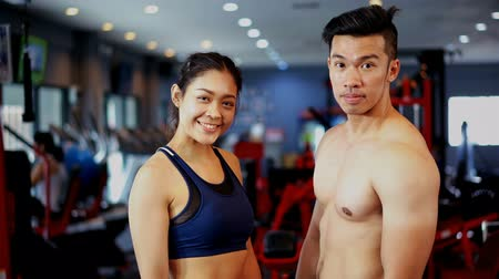 The female bodybuilder and Young muscular trainer man turn on face to smiling and looking at camera in fitness gym, fitness and healthy concept Stockvideo