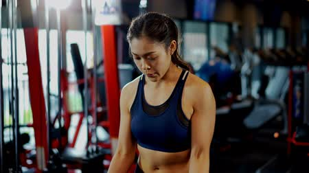 Tracking and close up shot with young bodybuilder female lifting heavy weight barbell in fitness gym,  Female muscular look athletic and has beauty muscle,  fitness and healthy concept Vídeos