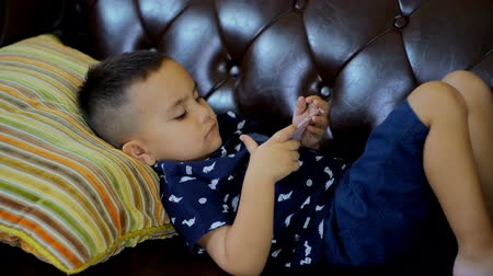 izle : Locked shot with a little mixed race boy lying on couch and watching smartphone in hand