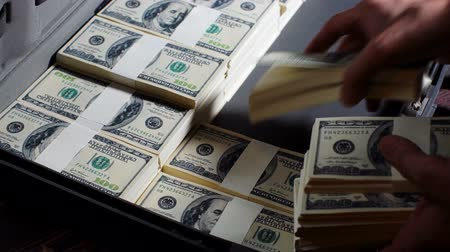 us banknotes : Men packing 100 US dollar bills in to briefcase