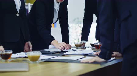 storming : 4K close up shot with business group standing and they are brain storming in a meeting, young businesswoman used pen pointing on confident document in conference room Stock Footage