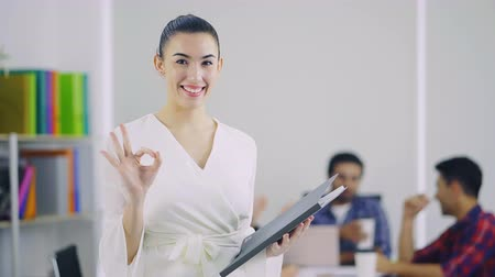 taça : 4K portrait shot of a beautiful young woman smiling warmly and raise her hand up the symbol OK to the camera. In the background busy office with working colleagues
