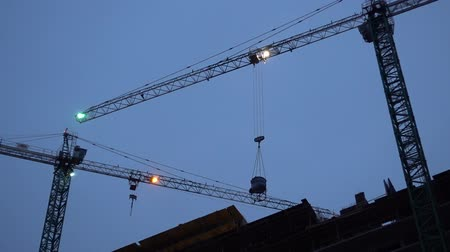 Construction Crane with a lights Works In The Evening. Стоковые видеозаписи
