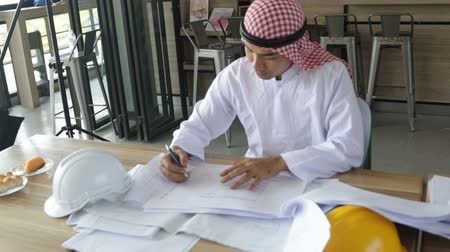 hardhat : Arabic businessman working with blueprint