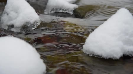 Stream with snow and ice in the winter woods