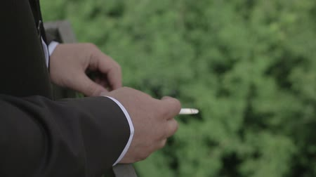 small businessman : a man smoking a cigarette on the balcony Stock Footage
