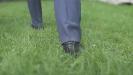 camurça : man in black shoes walking on the green lawn