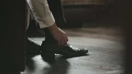 shiny : Man tying the laces on black shoes on a wooden floor hd Stock Footage