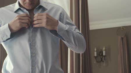 носить : Man adjusting shirt buttons.