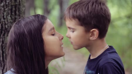 дружба : Portrait. A little boy is kissing with a little girl and hugging loving hard each other. Slow motion