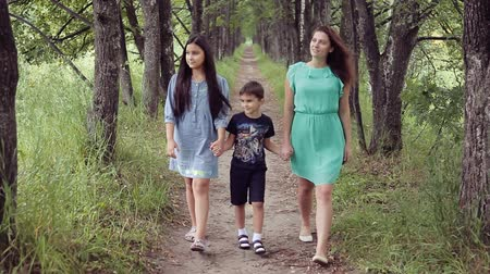 travessura : Happy mother with her daughter and son walking around the park smiling holding hands on a summer sunny day