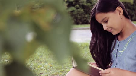 pictured : Portrait. A beautiful little girl with long hair reads a book sitting under a tree and dreams about something pleasant smiling Stock Footage