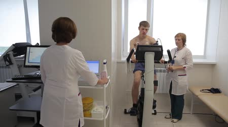 equipamentos esportivos : A team of medical doctors perfrorms an electrocardiographic study using an exercise bike