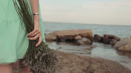 piwonia : Close-up. Slow motion. A girl is walking along the seashore with a bouquet of flowers. Wideo
