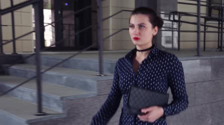 встреча : Close-up. Business duvushka goes next to the building with a bag in hand
