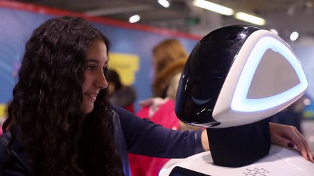 kafaları : The girl communicates with the robot and smiles. Girl and robot. Modern robotic technologies. Artificial intelligence. Cybernetic systems today. HD