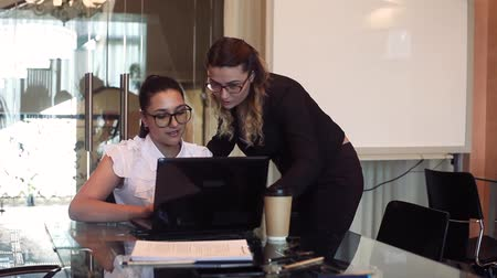 cooperar : Two business women discuss a business project in the office using a computer with a good mood