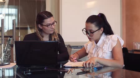 cooperar : A team of two business girls working on a business project in the office using a mobile computer.