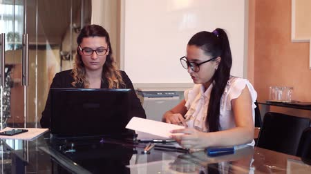 colegas : Two business women wearing glasses in business clothes discussing a business project in an office sitting at a table using a computer.