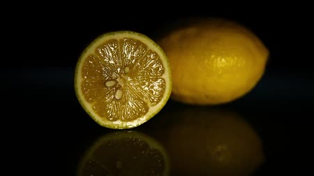 klín : Half a lemon and a whole lemon on a dark table. HD
